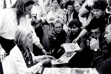 Woman gives autograph to journalists