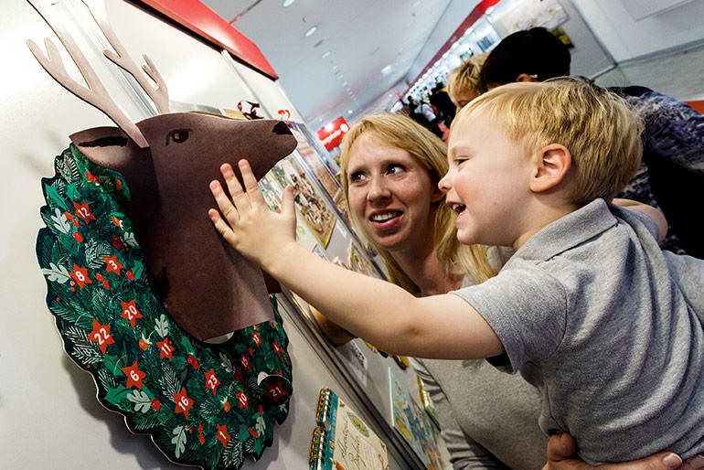 Woman holds a little boy and explores Frankfurt Book Fair