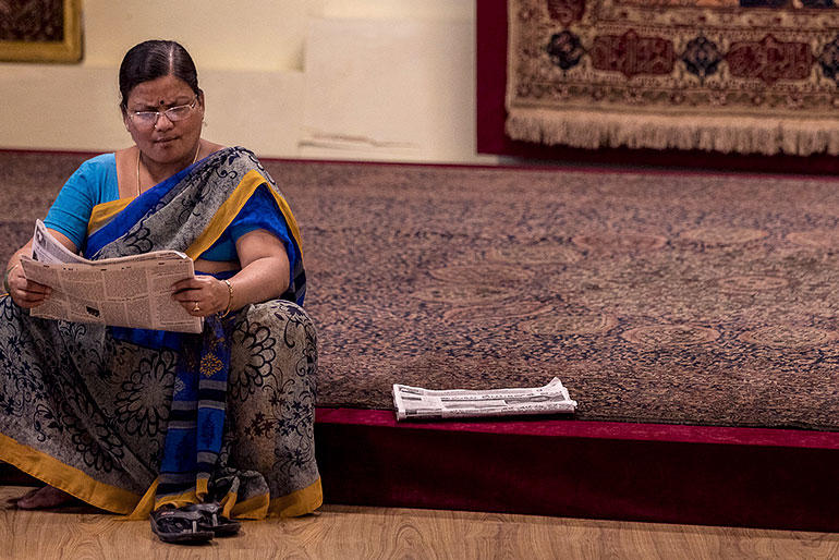 A woman sits on a carpet and reads in the paper