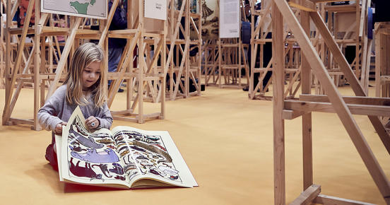 Girl sits on the ground and reads in her illustrated book