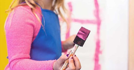 A girl paints a wall with a pink brush