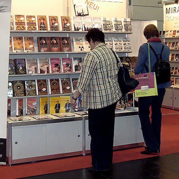 Women are standing in front of a book stand