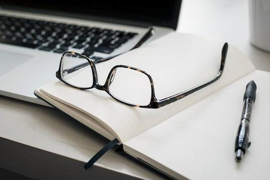 Glasses and a notebook are lying on a laptop