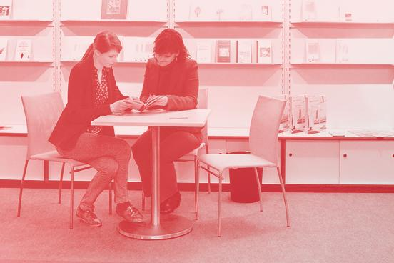 Two women reading a book at Frankfurter Buchmesse.